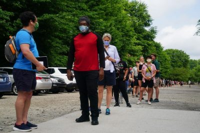 People stand in line outside, most of them wearing face masks that cover their noses and mouths. The line of people stretches far into the distance, and it's impossible to see the end.