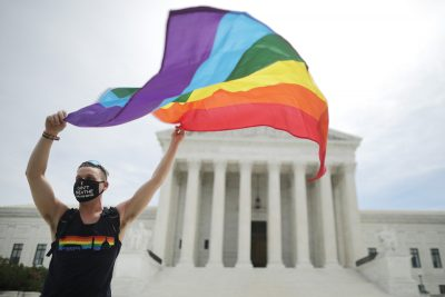 A white person stands outside the US Supreme Court building. They are wearing a mask and holding a rainbow Pride flag.