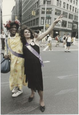 Marsha P Johnson, a black trans woman, and Sylvia Riveria, a Latina trans woman, stand together outside on a street in New York City.
