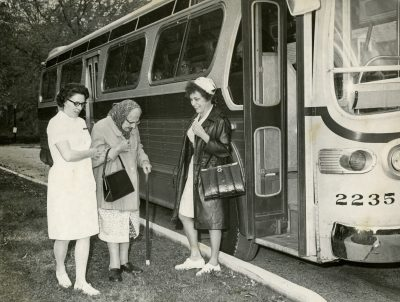 Outside a bus, two women dressed in nurse uniforms help an older woman get to the bus.