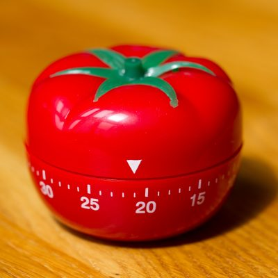 A red tomato shaped kitchen timer. It has numbers written on it to show how much time is left on the timer.