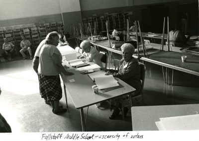 This image shows Fallstaff Middle School cafeteria where a polling site is set up. There are some people sitting at the tables to check in voters and some people signing in to vote.