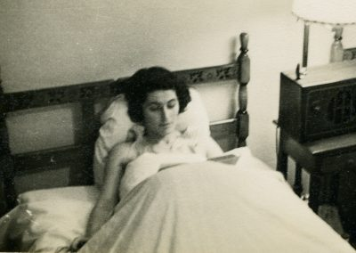 A woman sits in bed, reading a book. Her legs are covered by a blanket.et.