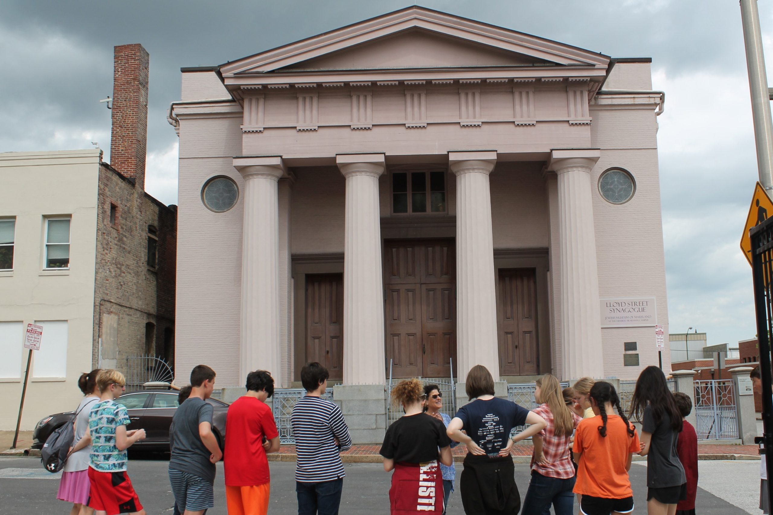 A group of young people stand outside the Lloyd Street Synagogue, a large building with columns and a pointed top. The group faces a tour guide who speaks to the group.