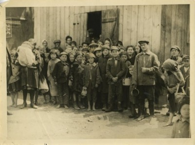 Black and white photograph of a group of orphans standing outside a barn, 1914-1919.  This photograph was used by the American Jewish Relief Committee to raise funds during World War I.  Courtesy of D.C. Liberles.  1980.29.5