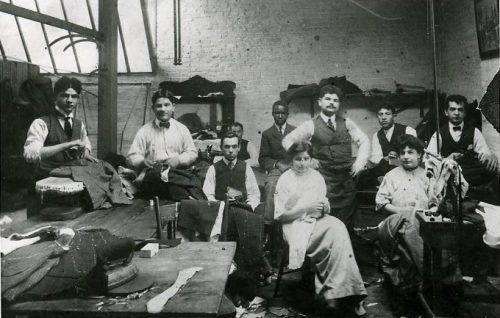 Black and white photograph of a group of workers in a tailor shop seated with piecework in their laps.