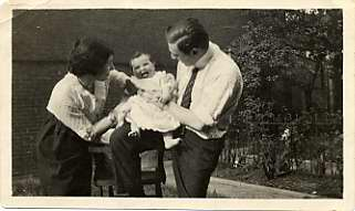 Man and woman with baby, posing outside.
