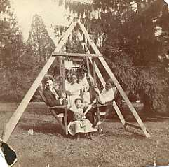 lack and white photograph of members of the Kraus Family on a lawn swing, n.d.