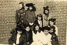 Black and white photograph of a group of school age girls standing in front of a brick wall, n.d.