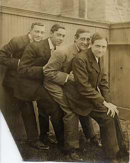 Black and white photograph of four young men leaning on one another in a back yard, n.d.