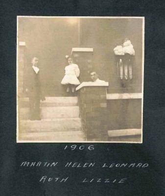 """Ruth Weinberg Leven compiled a photo album showing her family's everyday life in the early 20th century.  She carefully labeled each image with both the date and the first names of the participants.  In this 1907 photo, on the porch of their Baltimore home are Weinberg siblings Martin, Helen, and Leonard, with Lizzie, a young African American girl in what is probably a maid's or nanny's uniform, holding Ruth Weinberg in her arms. Unfortunately, Lizzie was not """"living in"""" in 1910, and so does not appear in the census (the servants listed in the household are white); more work must be done to identify her last name. Gift of Jan Weinberg. JMM 1996.127.23.51a"""