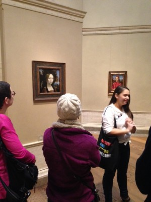 """A young woman stands in front of a painting while others look towards her. She is holding a tote bag that reads """"Museums are Fucking Awesome"""""""