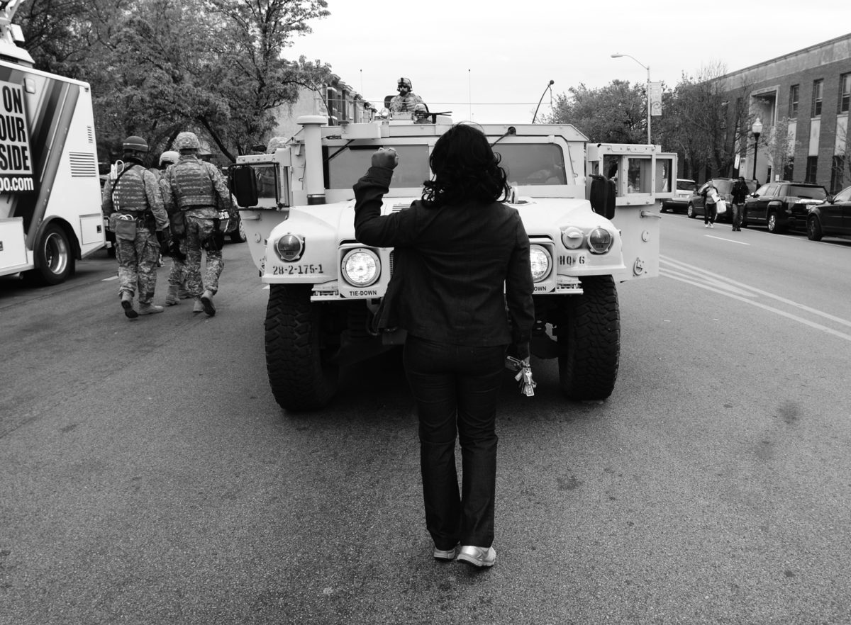 A black and white photo of a person standing in front of an armored truck, holding their fist up. They are turned away from the camera.