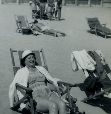 In this black and white image, a woman in a bathing suit, a hat, and a towel around her shoulders reclines in a folding chair on the beach. There are other people on the beach in the background of the image, also dressed in bathing suits and costumes.
