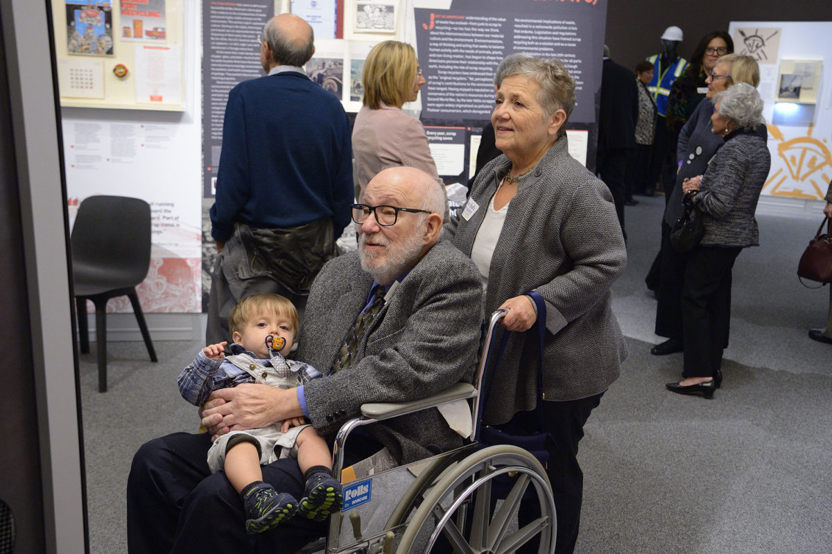 A group of people view the Scrap Yard exhibit. One, a white man with greying hair, sits in a wheelchair, holding a small child in his lap. A white woman stands behind the wheelchair, her hands on the handles.