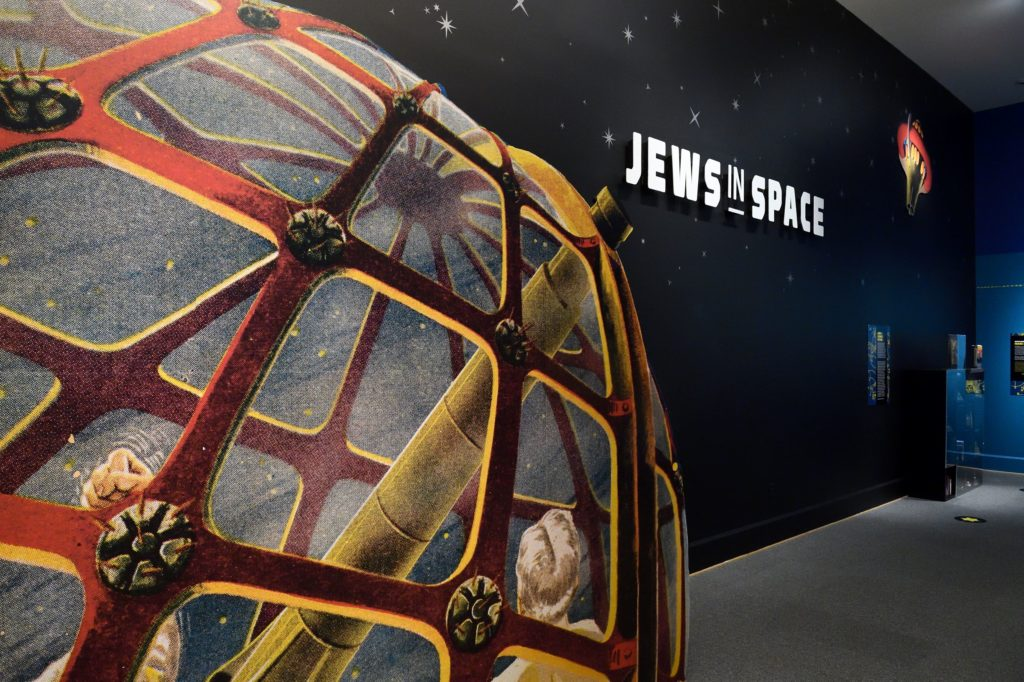 An interior photo of our Jews in Space exhibit, showing the feature wall that has an image of stars, the title Jews in Space, and old-fashioned illustrations of spacecrafts.