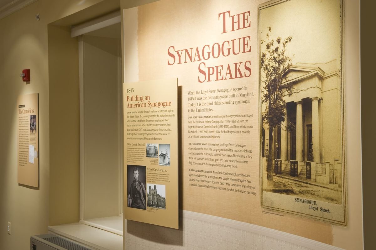 A panel in The Synagogue Speaks exhibit. The panel has text and images on it, including an early image of the Lloyd Street Synagogue. This exhibit is in the basement of the synagogue.