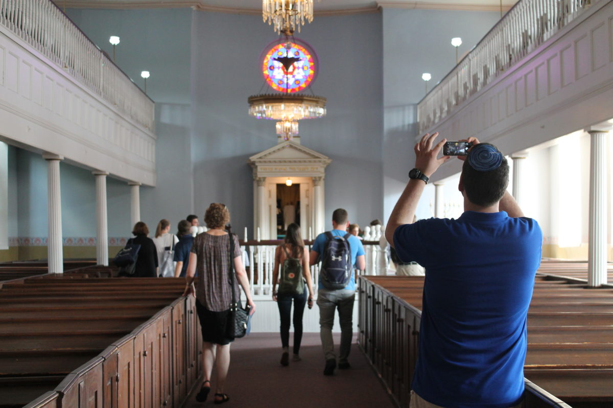 A group of visitors stand in the sanctuary of the Lloyd Street Synagogue, looking forward. A guest holds up his smartphone to take a picture.