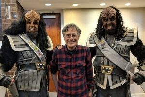 Marc Okrand, a white man with glasses and grey hair, stands in between two people cosplaying as alien characters from Star Trek. They have costume makeup, changing the shape of their head, long dark hair, and grey and silver costumes on.