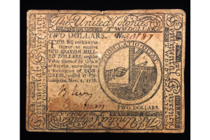 A photograph of an early two dollar bill. It was printed on paper that has aged significantly, and there's looping writing on it.