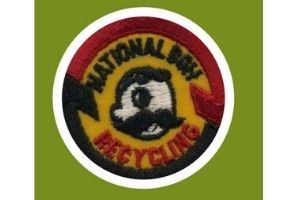 """A green square background. A photo of a patch that shows the National Bohemian logo. A cartoon illustration of a man with one eye and a large mustache in the middle with the words """"National Boh"""" in black thread, and """"Recycling"""" in red thread on the top and the bottom and arrows in black and red around the whole patch."""