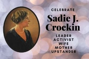 "An artistic background of blue, pink, and grey circles. A colored image of Sadie Cockrin, wearing a dark blouse, pearl necklace, and her hair pulled back, in profile on the left side. The words ""Celebrate Sadie J. Crockin: Leader, Activist, Wife, Mother, Upstander"" in black on the right side."