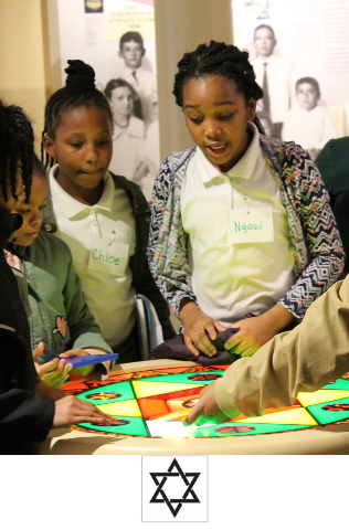 A group of students in the basement of the Lloyd Street Synagogue stand around the stained glass window hands on activity.