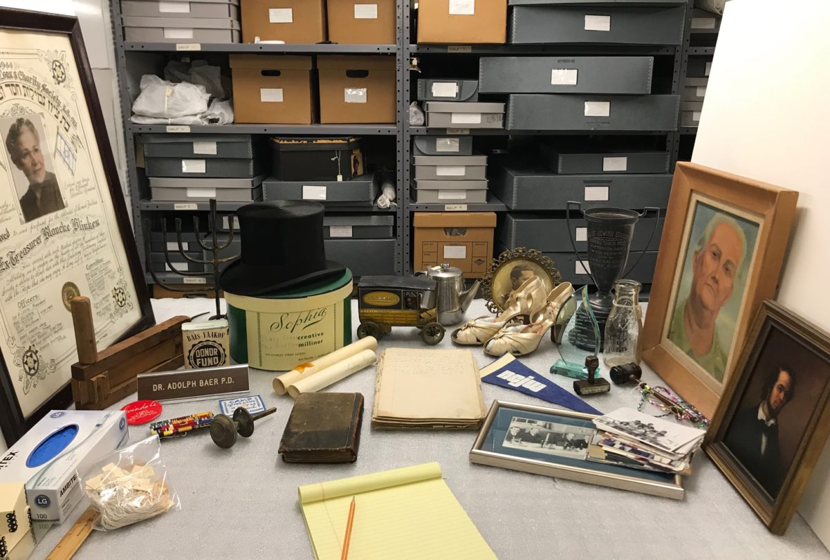An assortment of objects from our collections, including framed photos, a doorknob, shoes, glass bottles, and more. In the background are boxes stacked in shelves.
