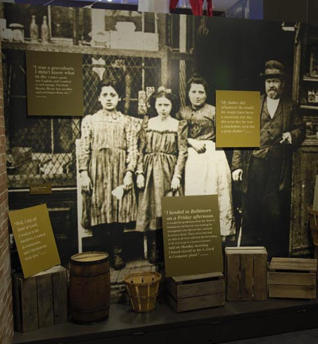 A wall in our exhibit showing an image of a family from the late 1800s, and text panels around the image and sitting on boxes.