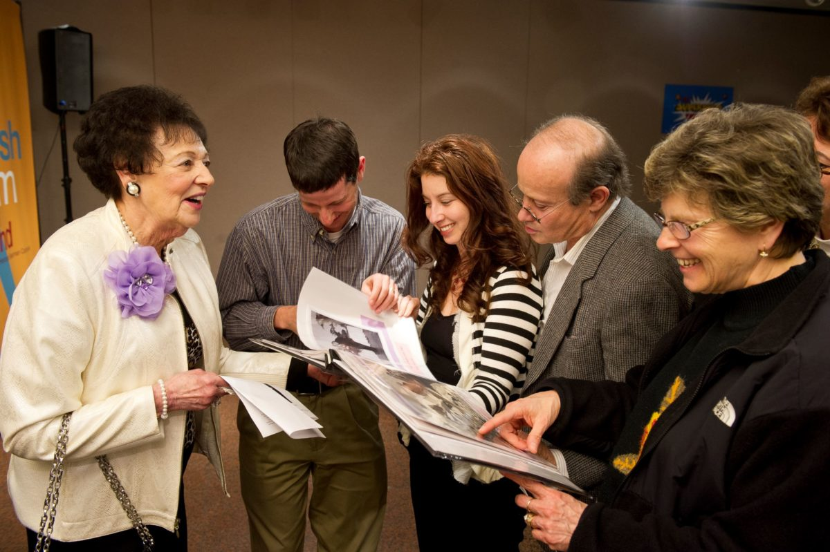 A group of people stand together talking and smiling. They look at a book filled with images. One person points to an image.