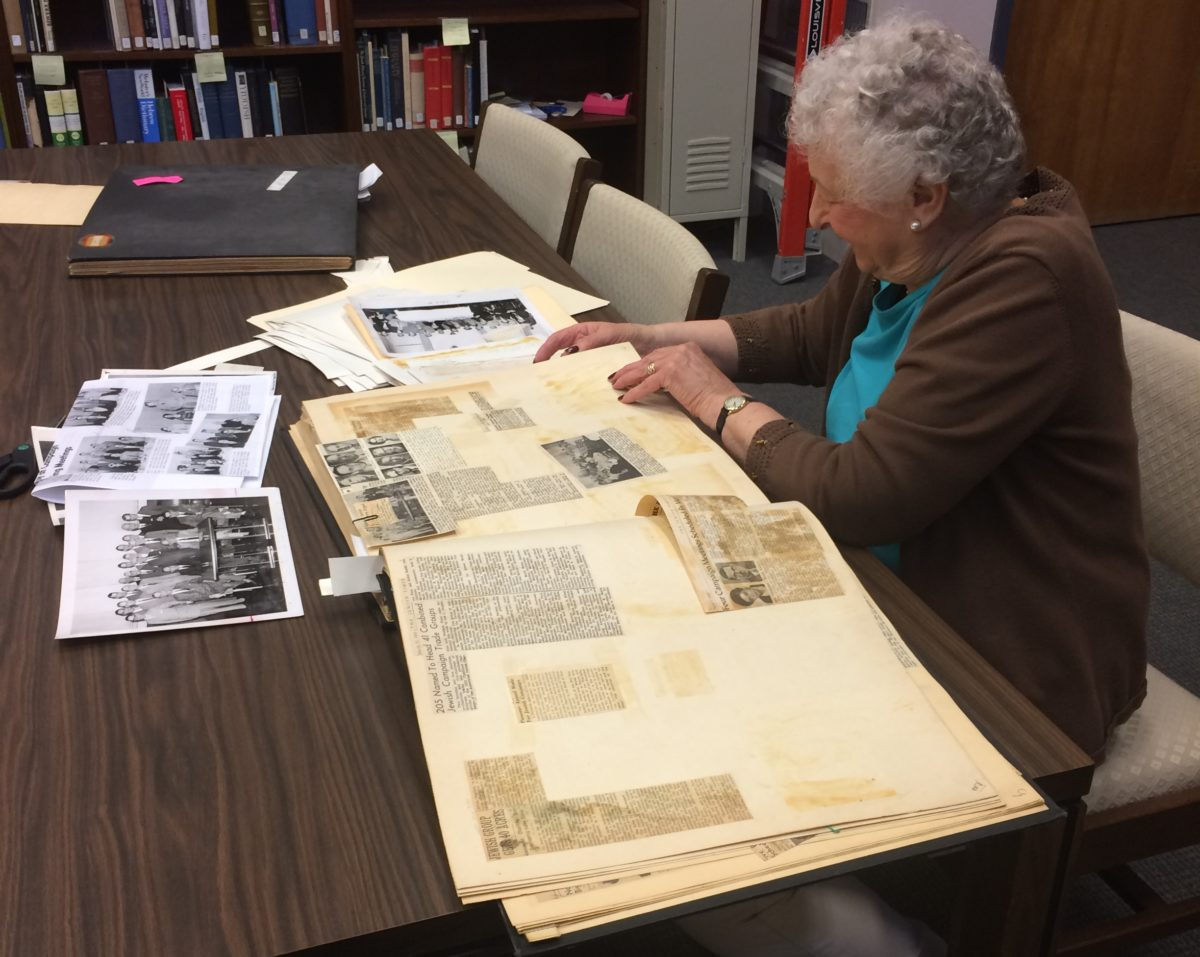 An archives volunteer sits at a table in the library. A scrap book is open on the table, filled with newspaper clippings. There are black and white printouts on the table.