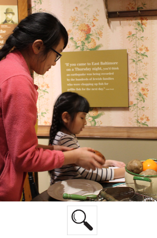 Two family members play with the fake food and kitchen utensils together in the Voices of Lombard Street exhibit.