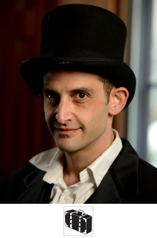 The actor that plays Harry Houdini, wearing a collared shirt, jacket, and top hat. He looks at the camera.