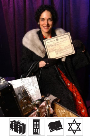 The actor that plays Ida Rehr, dressed up in old fashioned clothes and holding a certificate. She has a trunk open in front of her filled with items used during the performance. She smiles at the camera.