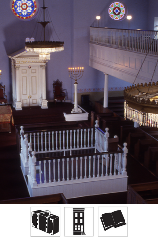 An interior photo of the Lloyd Street Synagogue from the second floor, showing the bimah, holy ark, chandeliers, and stained glass windows.