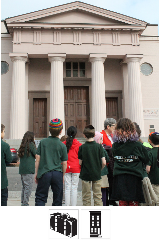 A group of students stand outside the Lloyd Street Synagogue, a large building with columns and pointed top. They look at the synagogue, listening to a tour guide.