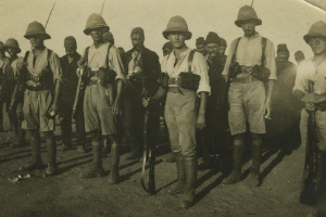 A sepia-tone photograph of a group of soldiers, dressed in uniform and wearing hats and carrying rifles, looking at the camera.