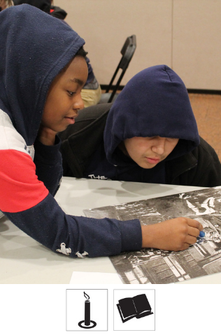 Two students sit at a table looking at a black and white image on the table. One student points to a spot in the image.