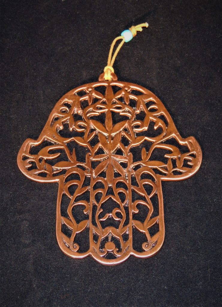 Bronzed Hamsa hung from the base of the palm. The laser cut Hamsa is decorated with pretty leaf designs.