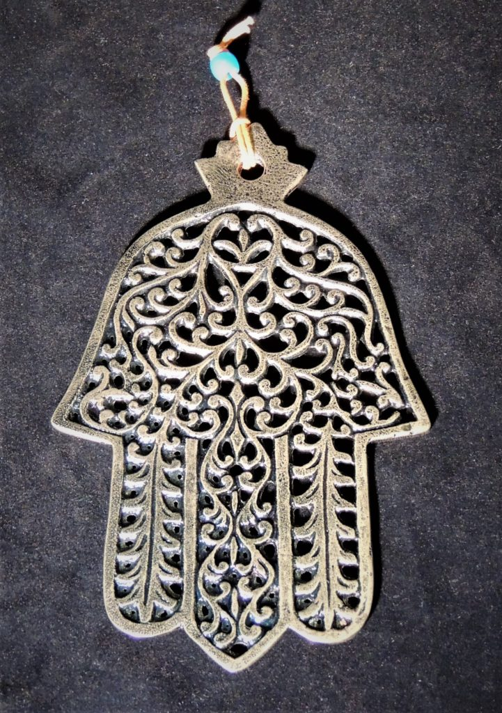 Laser cut silver pewter Hamsa with fauna inspired decorations. Hung from the palm.