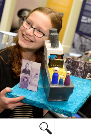 A student smiles and holds the project they made showing their family's history. It includes a hand-crafted boat, painted miniature people, and photographs of their family.