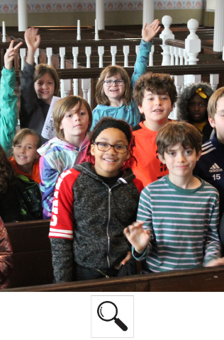 A group of young school children stand in the pews of the Lloyd Street Synagogue. Some are smiling, some are raising their hands.