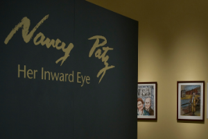 """A photo of the Nancy Patz exhibit, with the feature wall in black and the words """"Nancy Patz: Her Inward Eye"""" written in beige on it. There are two artworks framed on the wall in the background."""