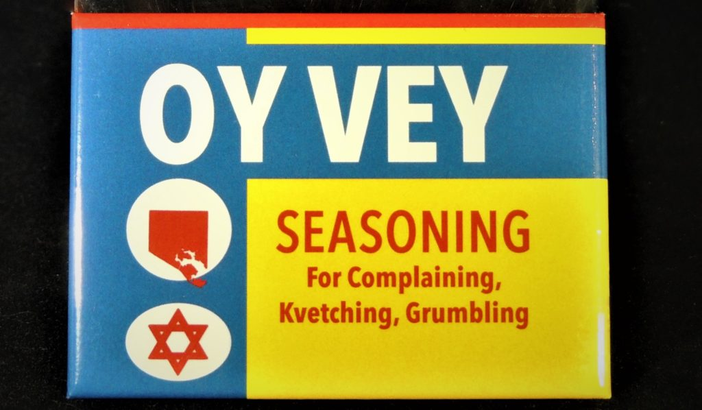 "Oy Vey! ""seasoning"" magnet replicating the colors of the classic Maryland spice, Old Bay (yellow, blue, red, and white). The icons feature an outline of Baltimore city and a Star of David."