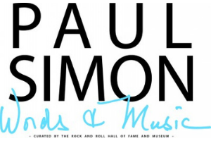 """A white rectangle with the words """"Paul Simon: Words and Music, Curated by the Rock and Roll Hall of Fame and Museum"""" written in black and light blue."""