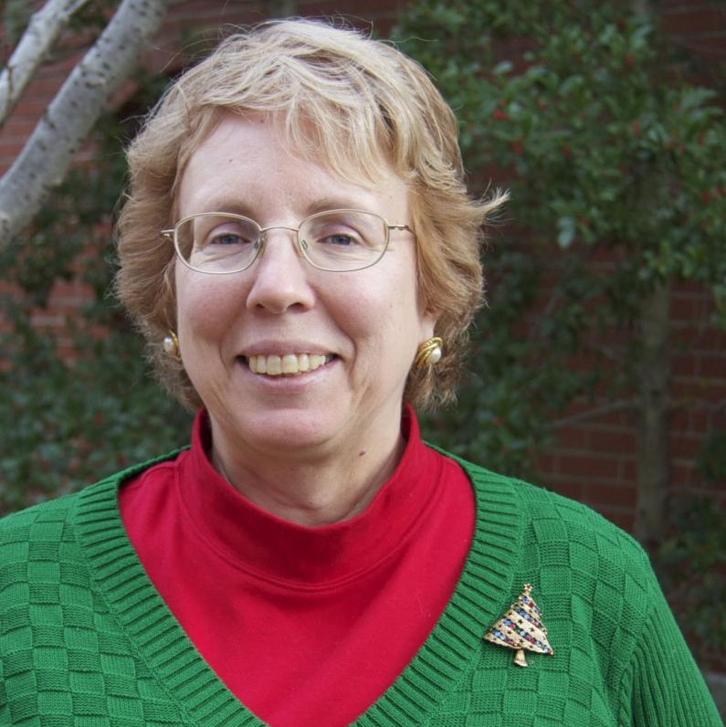 A white woman with short blonde hair, glasses, wearing a green sweater, red turtleneck, and pin. She stands in front of a tree in the brick courtyard. She is smiling.