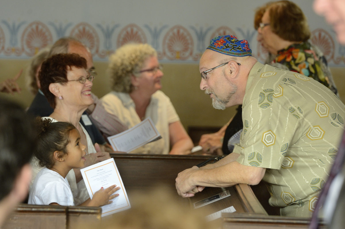 People sit in the pews of the Lloyd Street Synagogue. A man leans over the pew to speak to a young child, sitting next to a woman. They are all smiling.