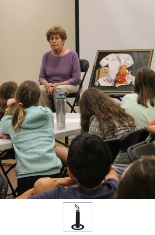 A group of students sit at a table, facing a woman. The woman is sitting, leaning forward, and has a framed picture next to her.