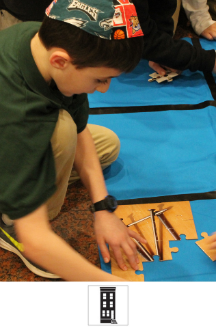 A student sits on the ground, working on a hands-on activity.