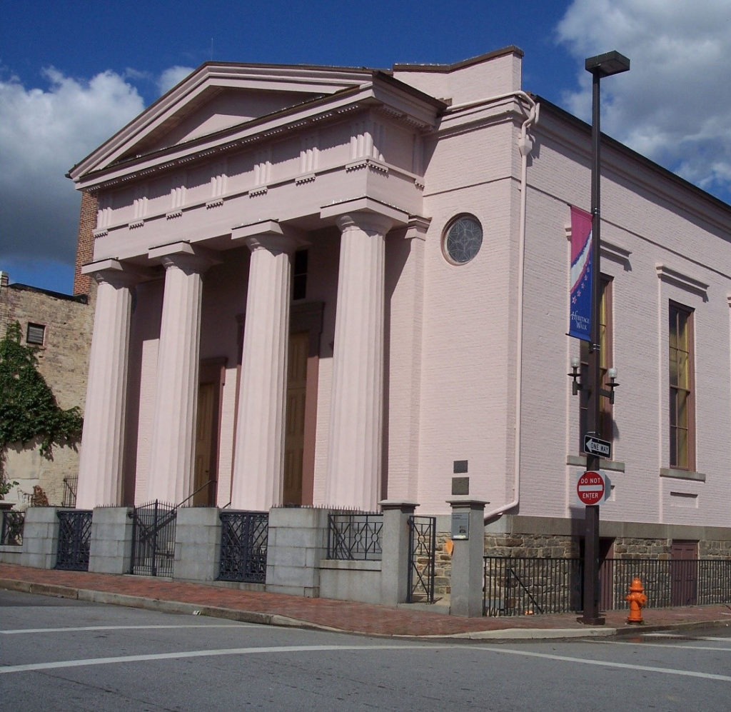 An exterior photo of the Lloyd Street Synagogue, a large building with columns and a pointed top.